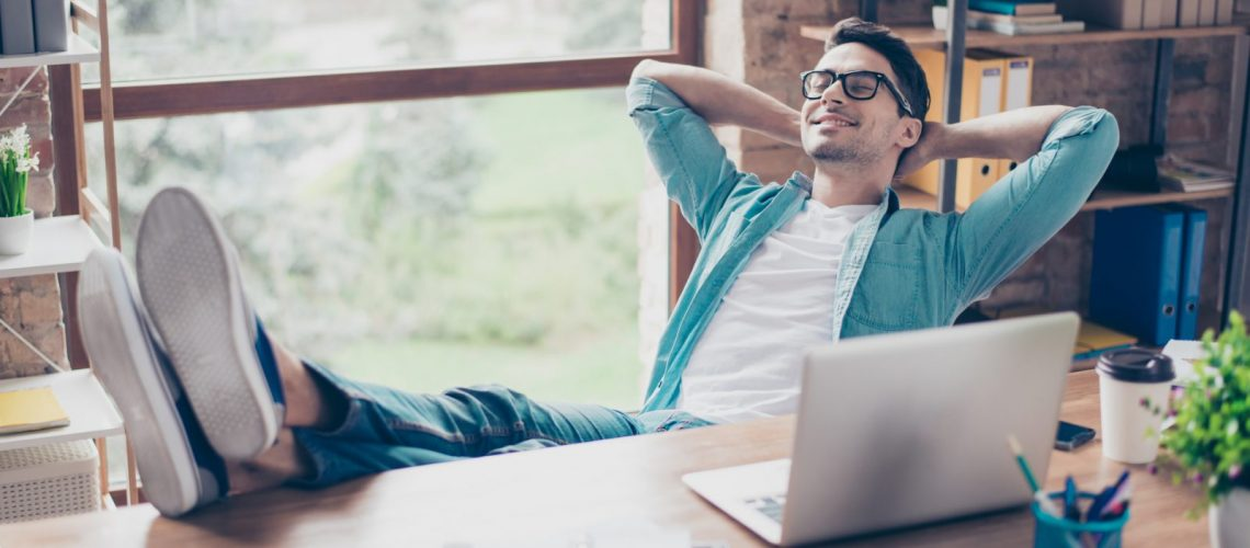 Happy calm smiling man having a rest after solving all the tasks at work