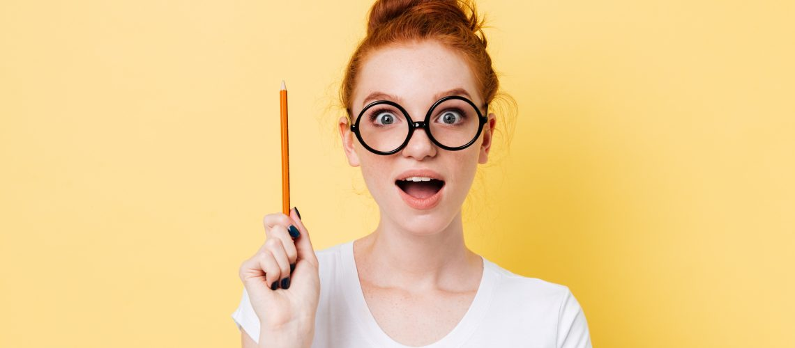 Happy ginger woman in eyeglasses having idea and looking at the camera over yellow background