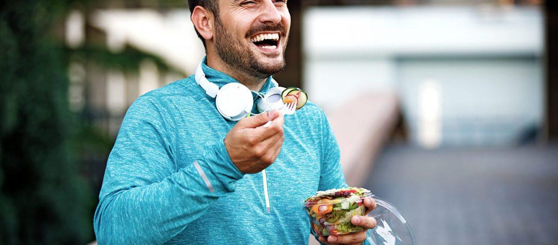 Sportlicher junger Mann mit Salat