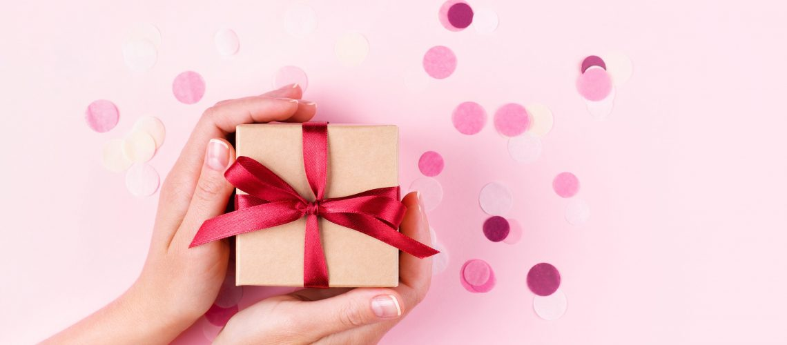 Woman's hands holding kraft gift box with red bow on pink background decorated with confetti.. Top view, holiday present concept with copy space, banner.