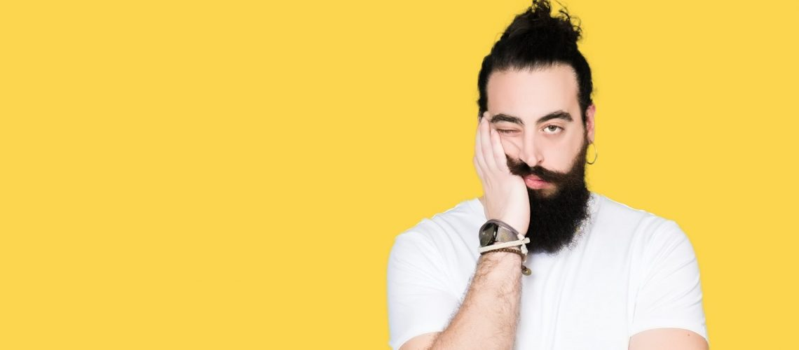 Young hipster man with long hair and beard wearing casual white t-shirt thinking looking tired and bored with depression problems with crossed arms.