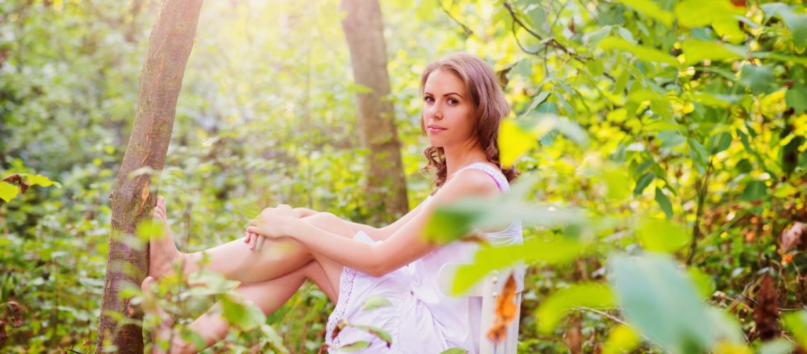 Attractive young woman sitting on a white chair in green forrest
