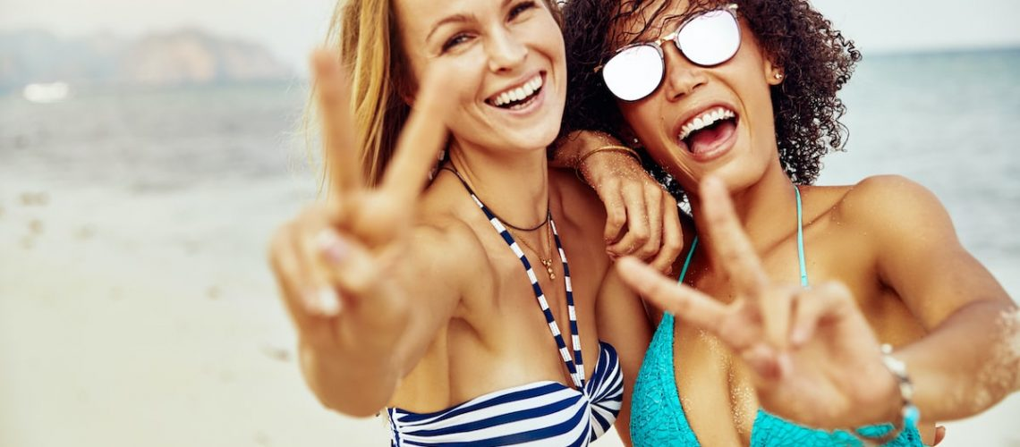 two-smiling-women-giving-the-peace-sign-on-a-AKPWNWT-min